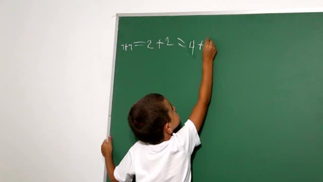 Jongen staande voor school blackboard of schoolbord.