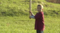 SM MS Boy standing in grass and holding baseball bat/ Bat slipping from boy's hands and hitting him in the face/ Boy rubbing face and smiling/ Chelsea, Michigan