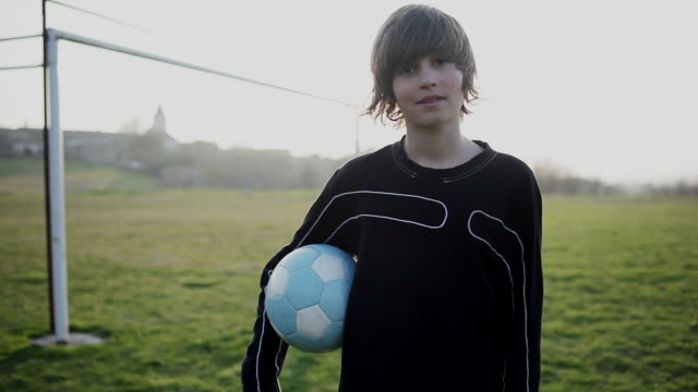 MS ZI Boy standing on ground with Football / Labastide de Levis, Midi-Pyrennees, France