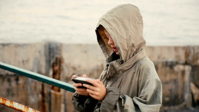 boy standing with smart phone on the sea promenade in the cold weather