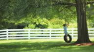 MS Boy (8-9) swinging on tire swing / Richmond, Virginia, USA