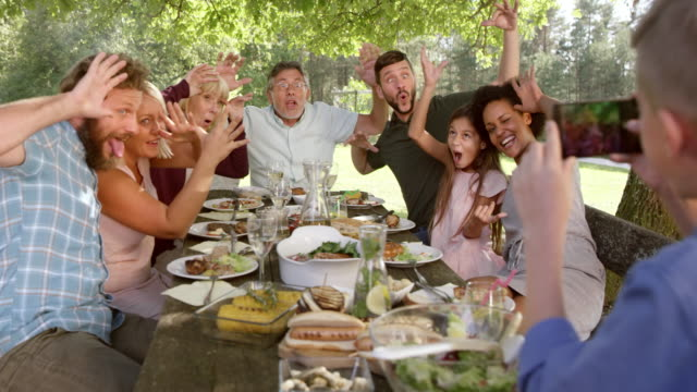 SLO MO Boy taking a funny picture of his family at a picnic