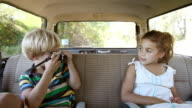 Boy taking a photograph of sister in car
