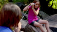 MS, SELECTIVE FOCUS, boy (10-11) talking to girl (8-9) on tin can phone sitting on rocks, Bovina, New York State, USA