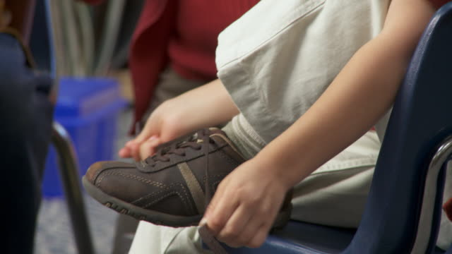 CU, TU, Boy (8-9) tying shoe laces in classroom, Richmond, Virginia, USA