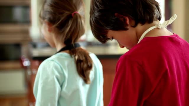 CU SELECTIVE FOCUS Boy (8-9) tying sister's (6-7) apron, Yarmouth, Maine, USA