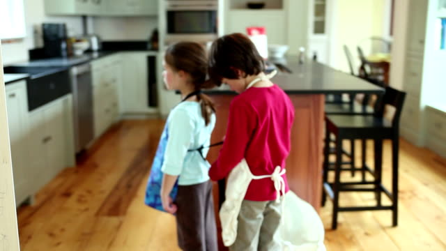 MS SELECTIVE FOCUS Boy (8-9) tying sister's (6-7) apron, Yarmouth, Maine, USA