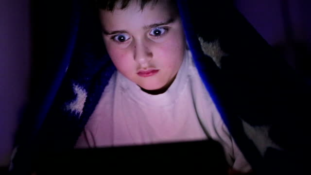 Boy under cover using tablet