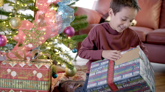 Boy unwrapping presents on Christmas tree