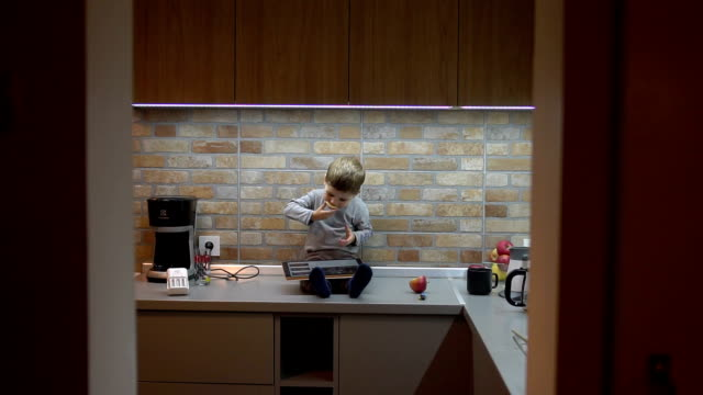 Boy using digital tablet in the kitchen