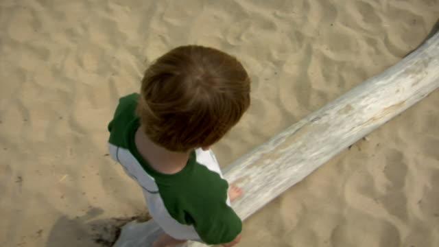 MS, HA, TS, Boy (8-9) walking on driftwood on beach, Provincetown, Cape Cod, Massachusetts, USA