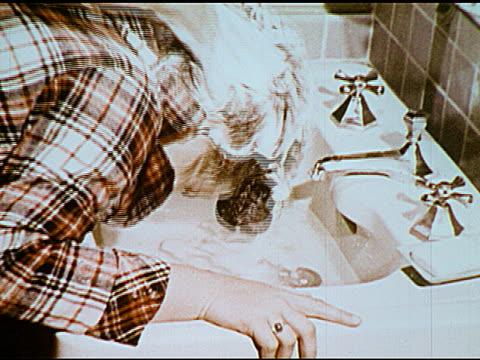 / Boy washing hair girl having hair washed in sink talking bar of soap man walking out of large building