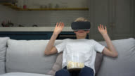 Boy watching a movie with vr glasses and eating popcorn