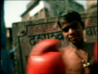 SOFT FOCUS MS boy wearing boxing gloves punching fists together / Varanasi, India