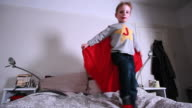 Boy wearing cape and jumping