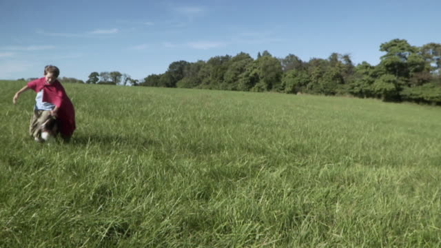 SLO MO WS Boy (2-3) wearing cape running with dog in meadow / Hampton, New Jersey, USA