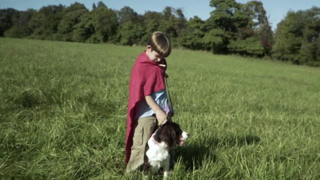 SLO MO WS Boy (2-3) wearing cape stroking dog in meadow / Hampton, New Jersey, USA