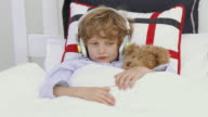 MS Boy (6-7) wearing headphones lying in bed with teddy bear / Cape Town, South Africa