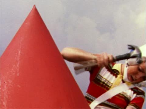 1959 boy wearing plastic helmet hammering nose cone of large homemade toy rocket / industrial