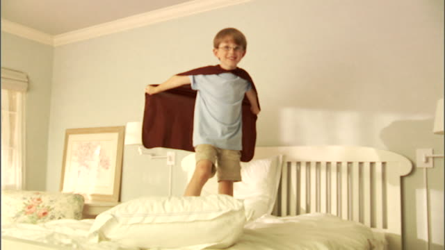 MS, Boy (6-7) wearing superhero cape jumping on bed