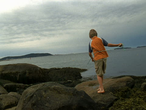 WS Boy whipping air with piece of rope on rocky coast/ Vinalhaven, Maine