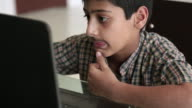 Boy with artificial mustache with working on laptop