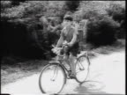 PAN boy with backpack riding bicycle away from tank on dirt road / West Germany / Cold War