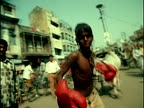 MS boy with boxing gloves throwing punches + running toward camera in crowded street / Varanasi, India