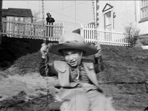 B/W 1955 HOME MOVIE boy with cowboy costume riding swing + smiling at camera