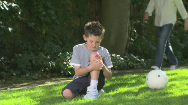 Boy with grazed knee, father enters scene and comforts him