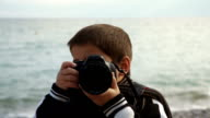 boy with photo camera makes a shoot on the bach