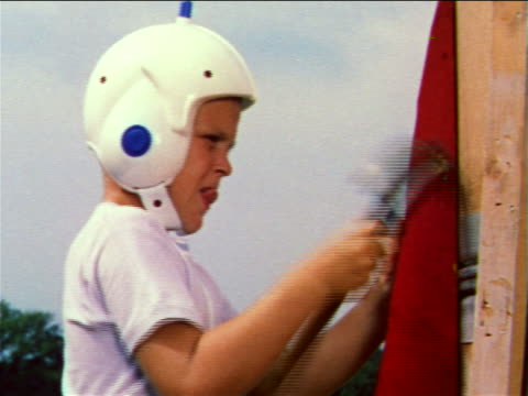 1959 boy with plastic helmet hammering fin of large homemade toy rocket / industrial