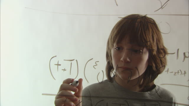 CU Boy working on math equation with marker on glass/ New York City