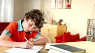 Boy writing in journal is happily interrupted by text message