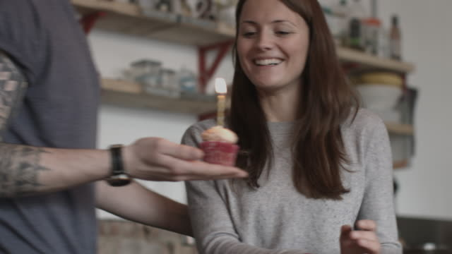 Boyfriend giving girlfriend a birthday cupcake