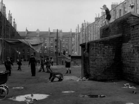 Boys climb on top of an old coal shed in the Gorbals area of Glasgow