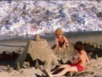 1959 2 boys on beach building sand castle with American flag on top / wave washes over it / industrial
