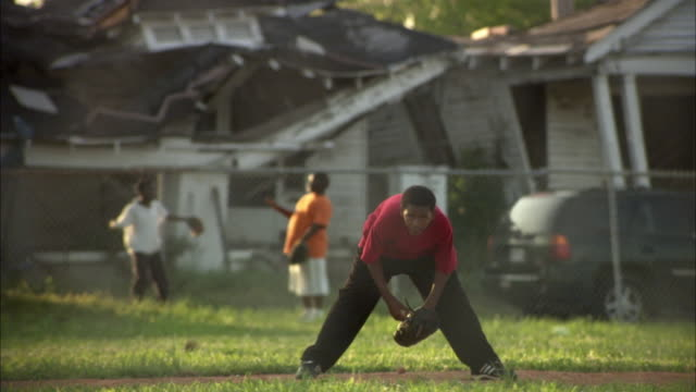 WS R/F Boys playing baseball, damaged house in background / New Orleans, Louisiana, USA