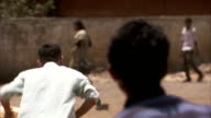 Boys playing cricket exemplifies a typical street scene of Mumbai. Available in HD
