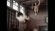 MONTAGE Boys practice trampoline in a gymnasium / UK