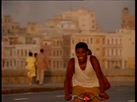 Boys riding bicycle along road by sea wall Havana; 1970's