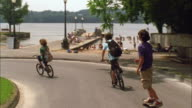 T/L WS TS Boys riding bikes and skateboarding down road to lake / Cazenovia, New York, USA