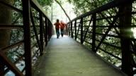 Jungen Laufen auf Fußgängerbrücke Hand In Hand