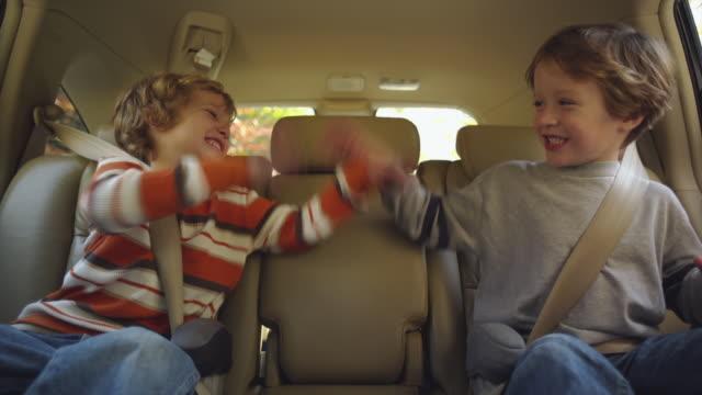MS Boys (4-5) sitting on back seat of car and pulling funny faces / Atlanta, Georgia, USA
