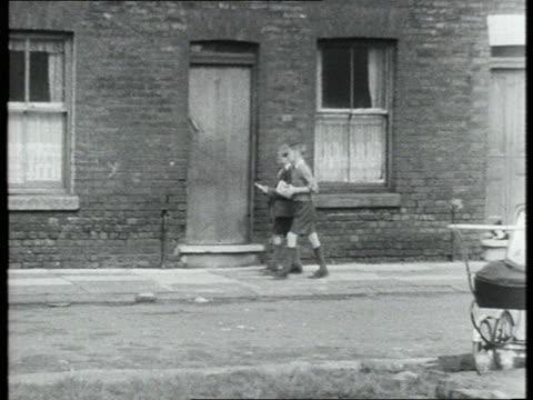 Boys walk along street past neighbours