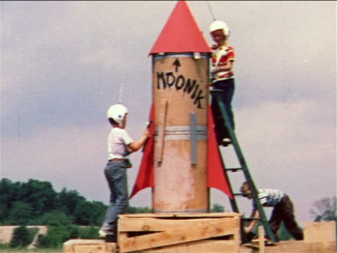1959 2 boys with plastic helmets working on large homemade toy rocket / boy pushing another on toy car