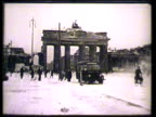Brandenburg Gate in Berlin w/ few pedestrians automobiles MS United States Government Issue men walking toward Red Cross club INT VS Males reading...