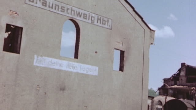 Braunschweig signs on railroad station and Third Reich logo on side of railroad car hastily painted over swastika crossed out with white paint and...