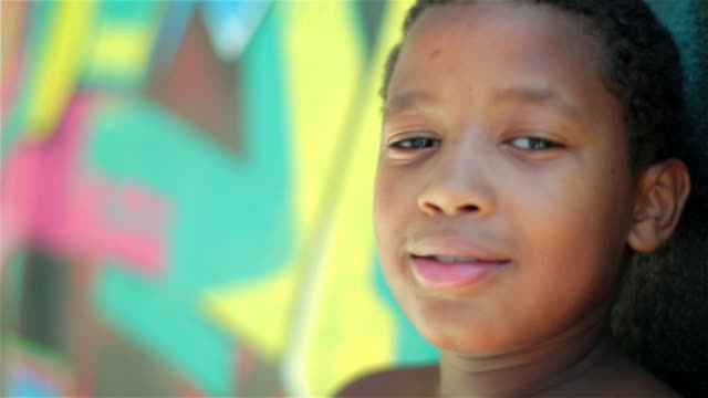 Brazilian boy looks at camera and smiles leaning against graffitied wall