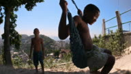 Brazilian boy on swing smiles at camera as friend watches and waits his turn